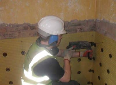 Operative installing a damp proofing course